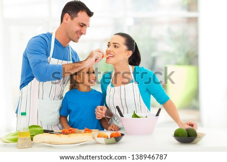 loving husband feeding wife a piece of tomato while cooking with daughter - stock photo
