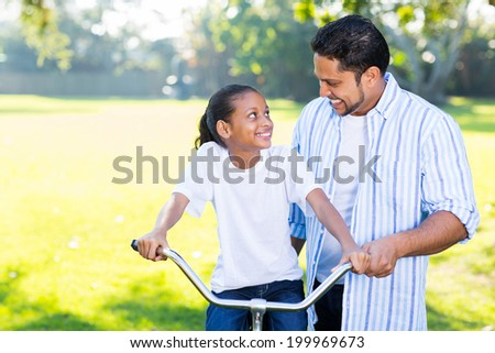 loving indian father teaching daughter to ride a bicycle at the park - stock photo