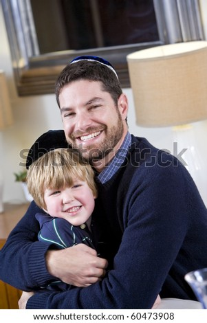 Loving Jewish father and young 4 year old son wearing yarmulkes - stock photo