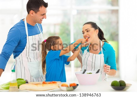 loving little daughter feeding mother a piece of tomato while cooking with father - stock photo
