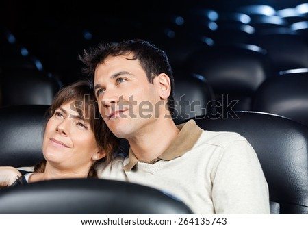 Loving mid adult couple watching movie in cinema theater - stock photo