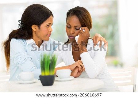loving middle aged african woman comforting her sad daughter at home - stock photo