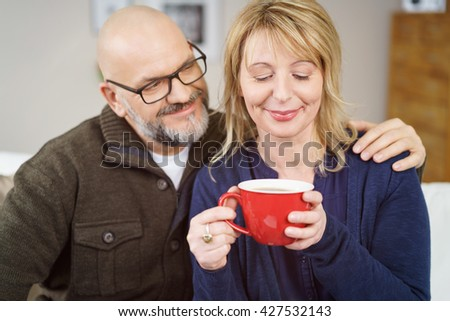 Loving middle-aged couple enjoying a cup of coffee while seated together on a sofa with the husband smiling as he watches his wife savoring the aroma - stock photo