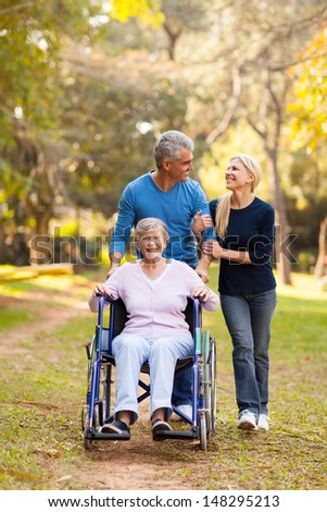 loving middle aged couple taking disabled mother for a walk outdoors - stock photo