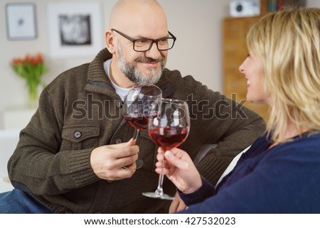 Loving middle-aged man and woman toasting each other with glasses of red wine as they relax at home on the sofa - stock photo