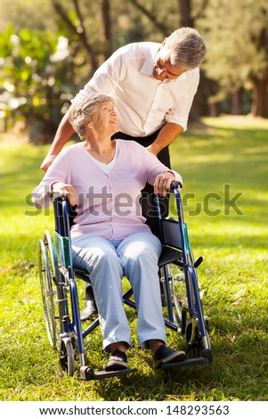 loving middle aged son taking his disabled mother for a walk at the park - stock photo