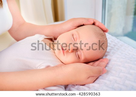 Loving mom hand holding cute sleeping newborn baby child.Mother holding head of her child  in hands. The baby on hands at mum.  - stock photo