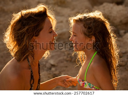 Loving moments of mother and child. Mom and girl on sunset - stock photo