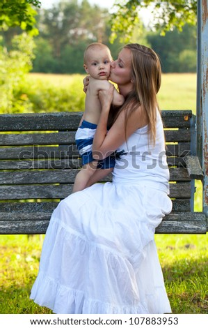 loving mother and child on a swing - stock photo