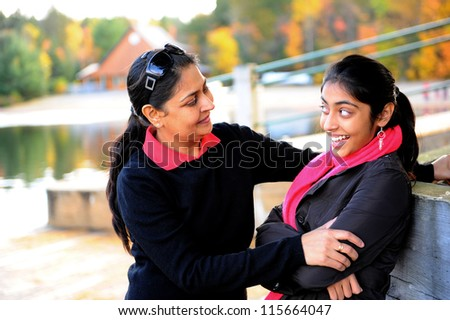 Loving mother and daughter talking to each other in outdoors - stock photo