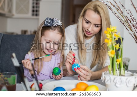 Loving mother and her daughter painting easter eggs. Cozy home atmosphere. Easter - stock photo