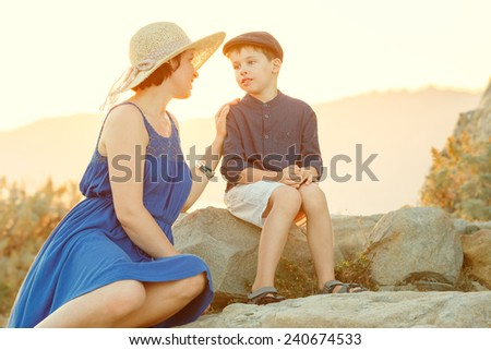 Loving mother and son talking outdoors on sunset during their summer vacation - stock photo