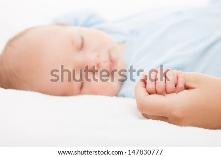 Loving mother hand holding cute sleeping newborn baby child - stock photo