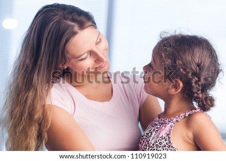 Loving mother looking at her daughter - stock photo