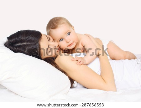 Loving mother lying with cute baby together on the bed at home - stock photo