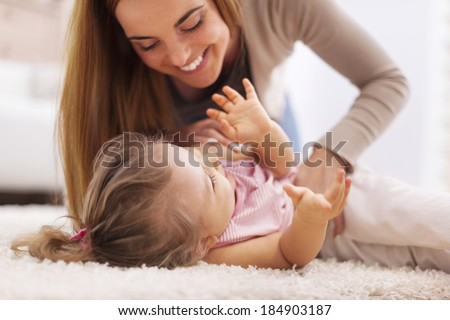 Loving mother playing with little girl on carpet   - stock photo