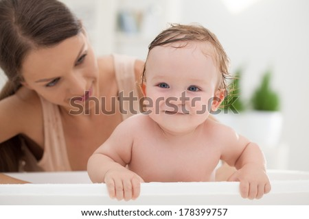 Loving mother washing her cute baby boy. - stock photo