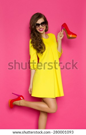Loving New Shoes. Happy young woman in yellow mini dress posing on one leg against pink background. Three quarter length studio shot. - stock photo