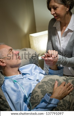 Loving old woman taking care of her sick husband - stock photo
