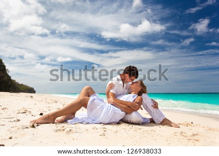 Loving pair sitting on the beach - stock photo