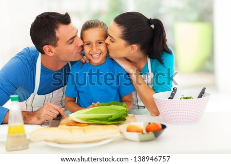 loving parents kissing little daughter in kitchen - stock photo