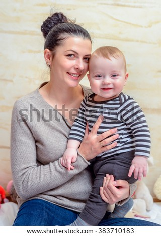 Loving portrait of a young mother with her adorable little blond baby clasped in her arms, both smiling happily and looking at the camera - stock photo