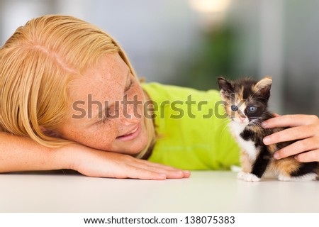 loving pre teen girl playing with her pet kitten - stock photo