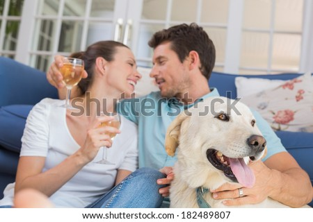 Loving relaxed young couple with wine glasses and pet dog sitting in living room at home - stock photo