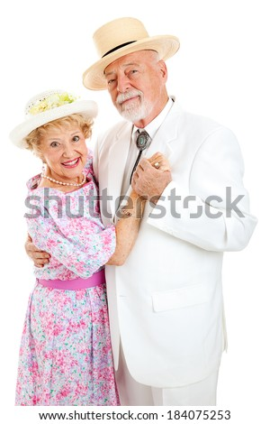 Loving senior couple in Southern style clothing dancing together.  White background.   - stock photo