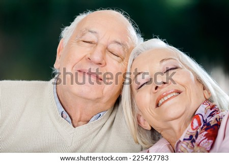 Loving senior couple relaxing with eyes closed at nursing home - stock photo
