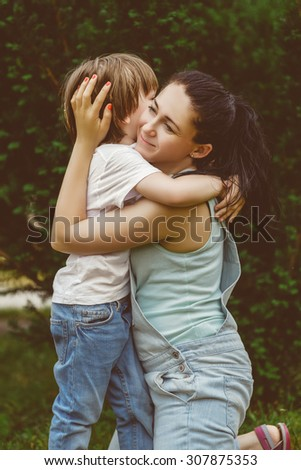 Loving son hugging his happy mother in park. Warm toned image - stock photo