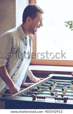 Loving this game. Side view of cheerful young handsome man playing foosball game and looking excited while standing in front of window - stock photo