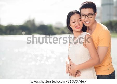 Loving Vietnamese couple hugging outdoors - stock photo