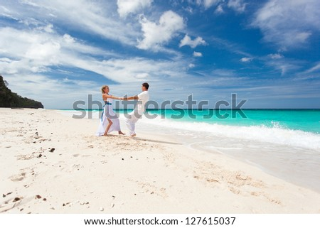 Loving wedding couple dancing on beach in white dresses - stock photo