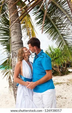 Loving wedding couple kissing under the palm - stock photo