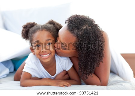 Loving woman  kissing her daughter lying down on bed at home - stock photo