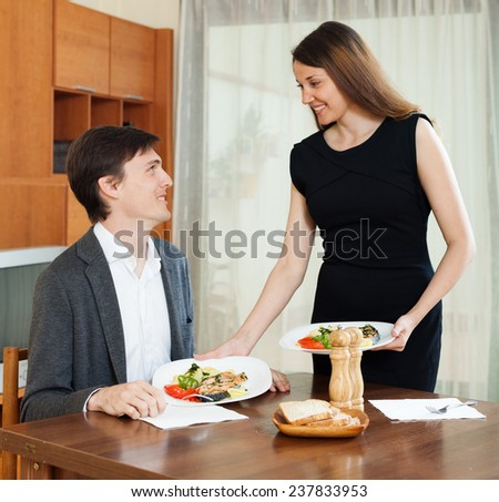 Loving woman serving dinner to beloved man at table - stock photo