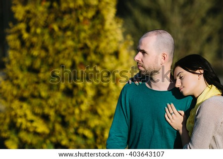 Loving young calm and serious couple sitting arm in arm with copy space - stock photo