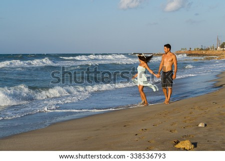 Loving young couple at the beach in a late summer hazy day at dusk, wearing a turquoise dress and shorts, enjoying  going barefoot in the ocean water, getting wet, teasing and kissing one another. - stock photo