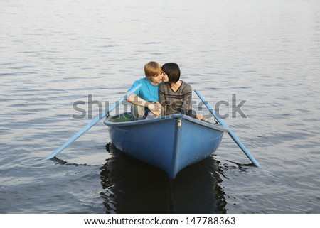 Loving young couple cuddling in rowboat at lake - stock photo