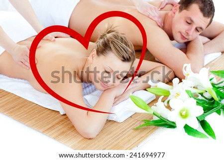 Loving young couple enjoying a back massage against heart - stock photo