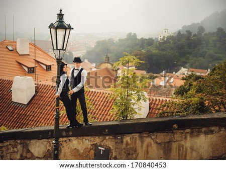 Loving young couple in front of Prague roofs. Kissing - stock photo