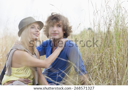 Loving young couple looking away while sitting in field - stock photo