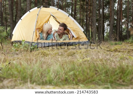 Loving young couple relaxing in tent - stock photo