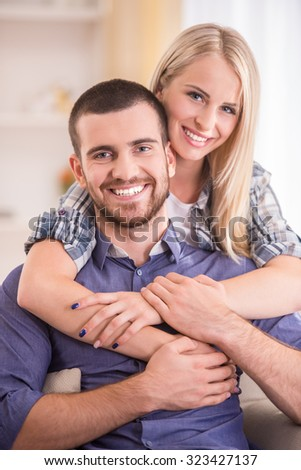Loving young couple sitting on the couch at home, look at the camera - stock photo