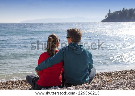 Loving young couple sitting on the white sand by sea, and enjoying each other , on windy sunny day, high, rough sea and bright blue sky in the background - stock photo