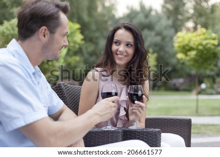 Loving young couple toasting red wine on chairs in park - stock photo