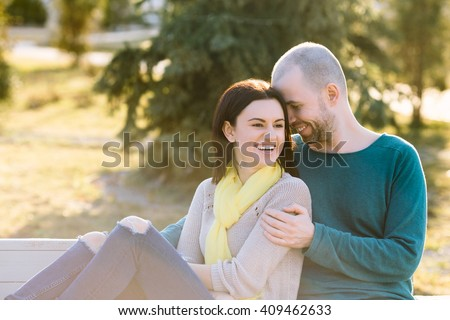 Loving young smiling couple boyfriend and girlfriend or husband with wife sitting on the bench in the park hug with copy space strong back light and lens flare cold toning - stock photo
