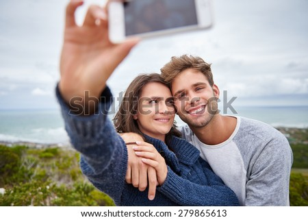 Loving young woman secretly smiling at her boyfriend while taking a selfie of them outdoors while he is smiling sweetly at the camera - stock photo