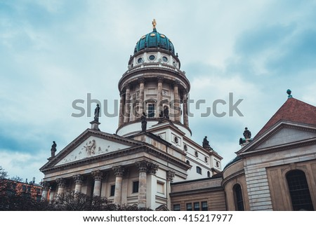 Low Angle Architectural Exterior of Front of Historical Landmark Cathedral Adorned with Dome and Gold Statues on Overcast Day with Heavy Storm Clouds in Germany - stock photo